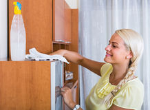 Blonde girl dusting in room and smiling Royalty Free Stock Photos