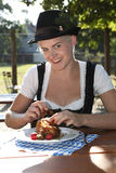 Blonde girl eats half chicken in a traditional beer garden Royalty Free Stock Photos