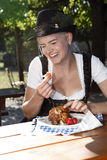 Blonde girl eats half chicken in a traditional beer garden Stock Image