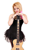 Blonde girl with electric guitar posing Stock Photo