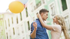 Blonde girl embracing beloved young man, couple dating, holding balloons Royalty Free Stock Images