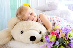 Blonde girl embracing big white teddy bear. Little cute blonde girl embracing big white teddy bear and bouquet of flowers indoors royalty free stock photography
