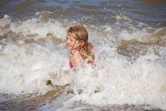 Blonde girl enjoying the waves. Young Girl enjoying playing in the sea and smiling Stock Photo