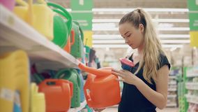 Young woman is watching a plastic watering can for gardening in a store. Blonde girl is examing a plastic watering can for pouring plants on a villa. She is stock video