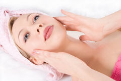 Blonde girl facial massage. On white background royalty free stock images