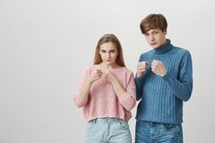 Blonde girl and fair-haired guy standing indoors with fists bunched and determined face expressions. Caucasian young. Blonde girl and fair-haired young men royalty free stock photography