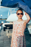 Blonde girl in flower dress and sunglasses holding  boat sails Royalty Free Stock Photography