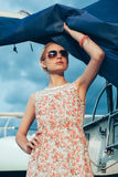 Blonde girl in flower dress and sunglasses holding  boat sails Royalty Free Stock Photos