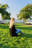 Blonde girl with flowers in her hands sitting on the green hill Royalty Free Stock Image