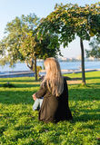 Blonde girl with flowers in her hands sitting on the green hill Royalty Free Stock Photos