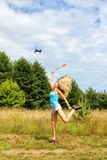 The blonde girl with a fly swatter drives away drone Royalty Free Stock Photos