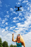 The blonde girl with a fly swatter drives away drone Stock Images