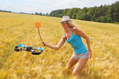 The blonde girl with a fly swatter drives away drone Stock Photos