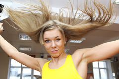 Blonde girl with flying hair jumping in gym. Beautiful Girl in Fitness Gym Photoshoot. More images of this models you can find in my portfolio Royalty Free Stock Photo