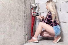 Blonde girl foreman tightens the nuts with wrench on control system of warm water floor in house under construction. Concept. Blonde girl foreman in white royalty free stock images