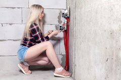 Blonde girl foreman tightens the nuts with wrench on control system of warm water floor in house under construction. Concept. Blonde girl foreman in white royalty free stock photos