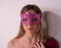 Blonde girl with fuchsia carnival mask over white background. Masquerade. Portrait of Beautiful Blond Woman in a Carnival Mask. Masquerade. Girl. Beauty royalty free stock image