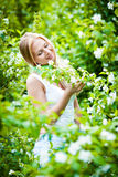 Blonde girl in the garden on a sunny day Royalty Free Stock Images