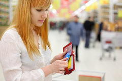 Blonde girl gets credit card from purse in store Royalty Free Stock Photos