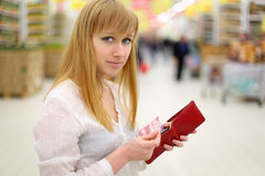 Blonde girl gets money from purse in store Stock Photos