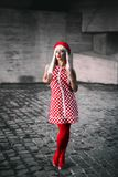 A blonde girl in a gingham dress. Fashion portrait of a blonde young girl in a gingham dress and red tights. Grey geometric abstract background Royalty Free Stock Photos