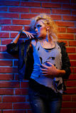 Blonde girl glam rocker. Portrait of beautiful glam rock style blonde girl posing near red brick wall Stock Photography