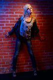Blonde girl glam rocker. Full-length portrait of beautiful glam rock style blonde girl standing near red brick wall Royalty Free Stock Photos