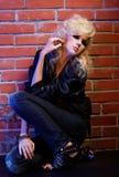 Blonde girl glam rocker. Portrait of beautiful glam rock style blonde girl sitting near red brick wall Stock Image