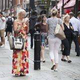 The blonde girl in glasses and long dress looking for information on her phone between a crowd Royalty Free Stock Photography