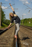 Blonde girl goes on rails Royalty Free Stock Photo