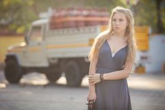 Blonde girl in gray dress stand on petrol station Stock Image