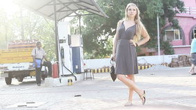 Blonde girl in gray dress stand on petrol station stock video