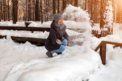 A blonde girl in a gray hat and a dark blue jacket in the winter in the forest is sitting in a snowdrift and throws her snow into royalty free stock photo