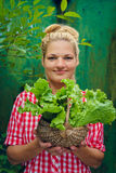 Blonde girl on a green background holding basket with lettuce Royalty Free Stock Photography