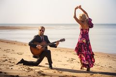 Blonde girl and guitarist on beach at low tide Royalty Free Stock Image