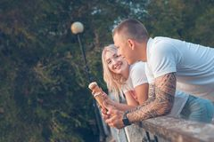 Blonde girl and a guy are standing with ice cream and smiling in the park. On a background of trees royalty free stock images