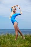 Blonde girl gymnast outdoors Stock Photos