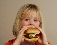 Blonde girl with hamburger. Royalty Free Stock Image