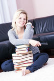 Blonde girl happily relaxing in the books. Stock Photography