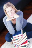 Blonde girl happily relaxing in the books. Royalty Free Stock Photography
