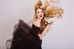 Blonde girl having fun, beautiful long curly hair in the air, young woman posing at studio. Funny look with opened mouth royalty free stock images