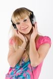 Blonde girl with headphones. On white stock photo