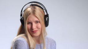 Blonde girl with headphones listening to music stock video
