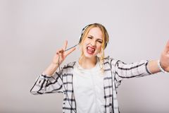 Blonde girl in headphones with tongue sticking out enjoys music and fools around dancing  on white background. Attractive young woman with curly hair listening royalty free stock image