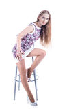 Blonde girl on high stool. Isolated on white Stock Photos