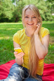 Blonde girl holding cell phone and listening music with headphon Royalty Free Stock Image