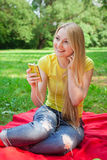 Blonde girl holding cell phone and listening music with headphon Stock Images