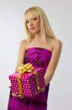 Blonde girl holding christmas gift. Beautiful blonde girl holding christmas gift in pink dress on grey background stock image