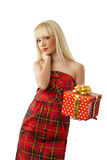 Blonde girl holding christmas gift in red dress. Beautiful young blonde girl holding christmas gift in red dress on white background Stock Images