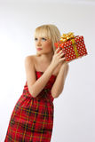 Blonde girl holding christmas gift in red dress. Beautiful young blonde girl holding christmas gift in red dress on grey background Royalty Free Stock Photos
